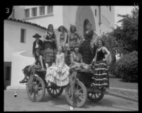 Dancers in the Old Spanish Days Fiesta seated on an old wagon at the courthouse, Santa Barbara, 1930