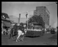 Float with costumed riders and flags in the parade of the Old Spanish Days Fiesta, Santa Barbara, 1930