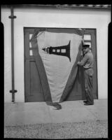 Point Vicente Lighthouse keeper Anton Trittinger with flag awarded for efficiency, Rancho Palos Verdes, 1935