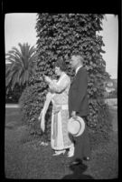 Man and woman standing near ivy-covered tree, [1920-1923?], rephotographed 1924