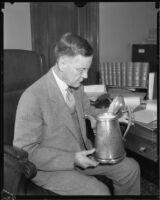Judge Charles D. Ballard holding metal pitcher, [1935-1939?]