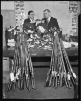Los Angeles County sheriff Eugene Biscailuz and Deputy County Counsel S.V.O. Prichard with guns collected as trial evidence, 1933