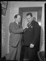 Beverly Hills police chief Charles C. Blair pinning medal on Captain Matt Vallance, [Beverly Hills?], [1937?]