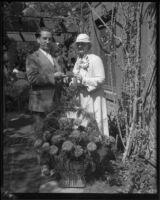 Horticulturist Harry L. Bateson, Mrs. Queen Boardman, and zinnia named for Queen Boardman, Los Angeles, 1933
