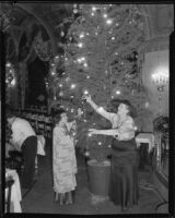 Mrs. Queen Boardman and Lugo Machio decorating Christmas tree, [1934?]