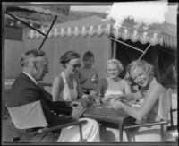 Alfonzo Bell, Elizabeth Tingle, Mrs. Miles Gray and Minnewa Bell playing cards at the Bel-Air Bay Club, Los Angeles, circa 1935-1936