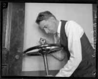 Los Angeles police sergeant Howard L. Barlow inspecting car steering wheel, 1927