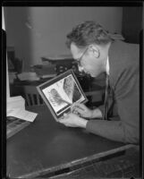 Los Angeles police captain Howard L. Barlow inspecting fingerprint images, Los Angeles, 1934
