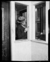 Los Angeles police sergeant Howard L. Barlow dusting window frame for fingerprints, Los Angeles, 1927