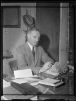 Col. Robert A. Bringham seated at his desk, Los Angeles, 1935
