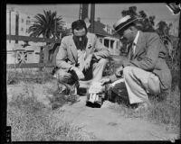 Detectives Thad Brown and Joe Filkas inspect fake bomb, Los Angeles, 1934