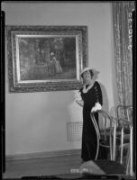 "Hersee Moody Carson standing next to a painting attributed to Marie-François-Firmin Girard titled ""Woman at the Well,"" Los Angeles, 1935"