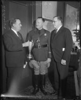E. Raymond Cato with C. C. Teague as he presents an award to Captain H. C. Meehan in Exposition Park, Los Angeles, 1934