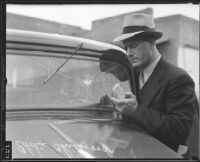 Captain Eddie Chitwood inspects his shattered windshield, Los Angeles, 1935