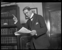 Distric Attorney Thomas Lee Woolwine reads papers with finger pointed in gesture, Los Angeles, 1920-1923