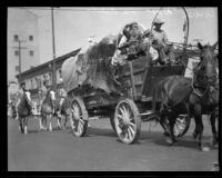 William Parmalee rides in a covered wagon at the La Fiesta de Los Angeles parade, Los Angeles, 1931