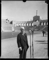 Joseph Scott speaks into a microphone on the field of the Memorial Coliseum, Los Angeles, 1930s