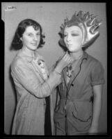 Otis Art Institute student Grace Mallon adjusts mask on fellow student Miriam Hazard before the annual student exhibition, Los Angeles, 1933