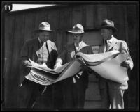 Three geologists and/or civil engineers examine an engineering drawing shortly after the failure of the Saint Francis Dam, [San Francisquito Canyon (Calif.) ?], 1928