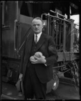 L. A. Downs, president of the Illinois Central Railroad, at railroad station wih citrus fruit, 1926-1938