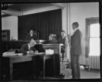 Judge, clerk, lawyer and witness in a courtroom, (Los Angeles?), 1920-1939