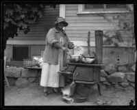 Woman cooking outside of her house after the Long Beach earthquake, southern California, 1933