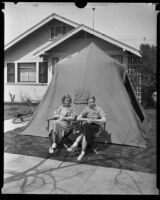 Two teenage girls seated outside of a tent in front of a house after the Long Beach earthquake, Southern California, 1933