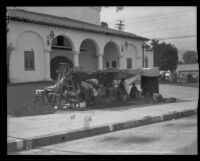 Family camped beneath a tarp in front of a church(?) after the Long Beach earthquake, Southern California, 1933
