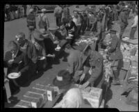 People in line holding plates of food after the Long Beach earthquake, Southern California, 1933