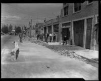 Workers clearing brick rubble from a sidewalk after the Long Beach earthquake, Southern California, 1933