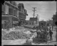 Clean-up crew beside building missing its facade after the Long Beach earthquake, Southern California, 1933