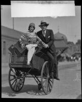 Gus Edwards and Senorita Armida atop a luggage cart, 1928