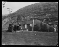 A turned-over car and destroyed house of the Sunset Canyon fires, Los Angeles, 1927