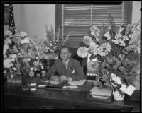 Buron Fitts sits at his desk with flowers, Los Angeles, 1927-1939