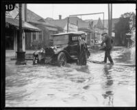 Man crossing flooded Pico Blvd. to get to car, Los Angeles, 1926