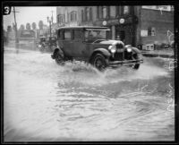Automobile driving down flooded street during rainstorm, [Los Angeles County?], 1926