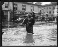 Policeman carrying woman across flooded street, [Los Angeles County?], 1926