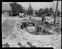 Automobile covered in mud left by January flood waters, La Crescenta-Montrose, 1934