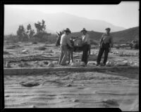 Three men and a burro in a flood-ravaged landscape, La Crescenta-Montrose, 1934
