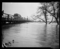 Norwalk bridge spanning the San Gabriel River swollen with rainstorm flooding, [Norwalk?], 1927