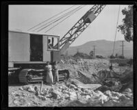 Lorraine Geise and Helen Potts standing next to a steam shovel on the first day of flood control work, La Crescenta-Montrose, 1935