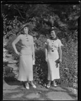 Mary Gene Hutters and Mrs. Wendell Hatteroth pose wearing stylish knitwear and hats at a party hosted by the Assistance Guild, Los Angeles, 1935