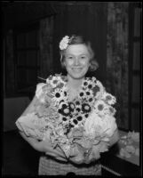 Lillian Reynolds holds an armful of artificial flowers at an exhibit of arts and crafts and hobbies, Los Angeles, 1935