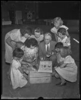 Dr. William L. Lloyd, naturalist, showing a collection of stuffed birds and other specimens to his young audience, Los Angeles, 1935
