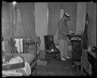 A. J. Fitzgerald, investigator, searching the room of William F. McKee who committed suicide, 1935