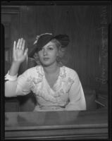 Actress Grace Bradley being sworn in on a witness stand, Los Angeles, 1935