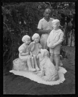 Ernest Yerbysmith standing next to his sculpture of 3 children with their dog, Los Angeles, 1935