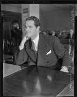 Henry Guttman, accused of theft, leans his chin on his hand as he sits in the courtroom, Los Angeles, 1935