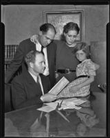 Archie Carter, Gladys Carter, and Virginia Carter look over some paperwork with Attorney Donald MacKay, Los Angeles, 1935