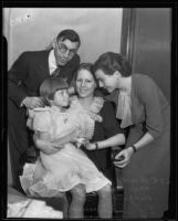 Virginia Carter sits on her mother's lap with their lawyers Anna Zacseck and Ed Haumsech standing next to them, Los Angeles, 1935